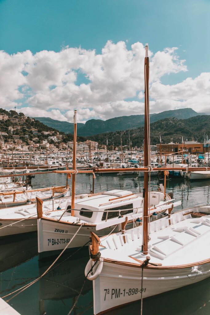 Einige Boote angedockt am Port de Sóller mit Bergen und Dörfern in der Ferne auf Mallorca.