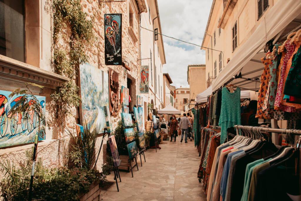 Gemälde und Kleidung ausgestellt für den Verkauf auf dem Wochenmarkt im Dorf Sineu auf Mallorca.
