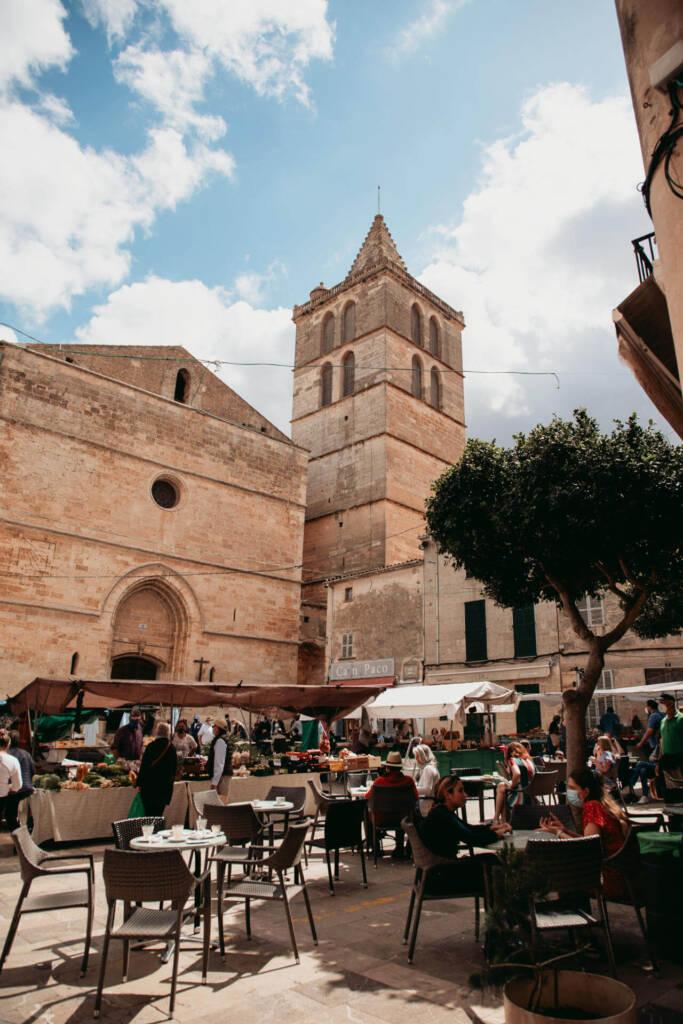 Ein gut besuchtes Café auf dem Wochenmarkt von Sineu auf Mallorca mit einem Gemüsestand und altertümlichen Gebäuden im Hintergrund.