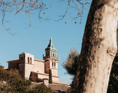 Blick auf die Kartause mit grünem Dach inm mallorquinischen Ort Valldemossa.