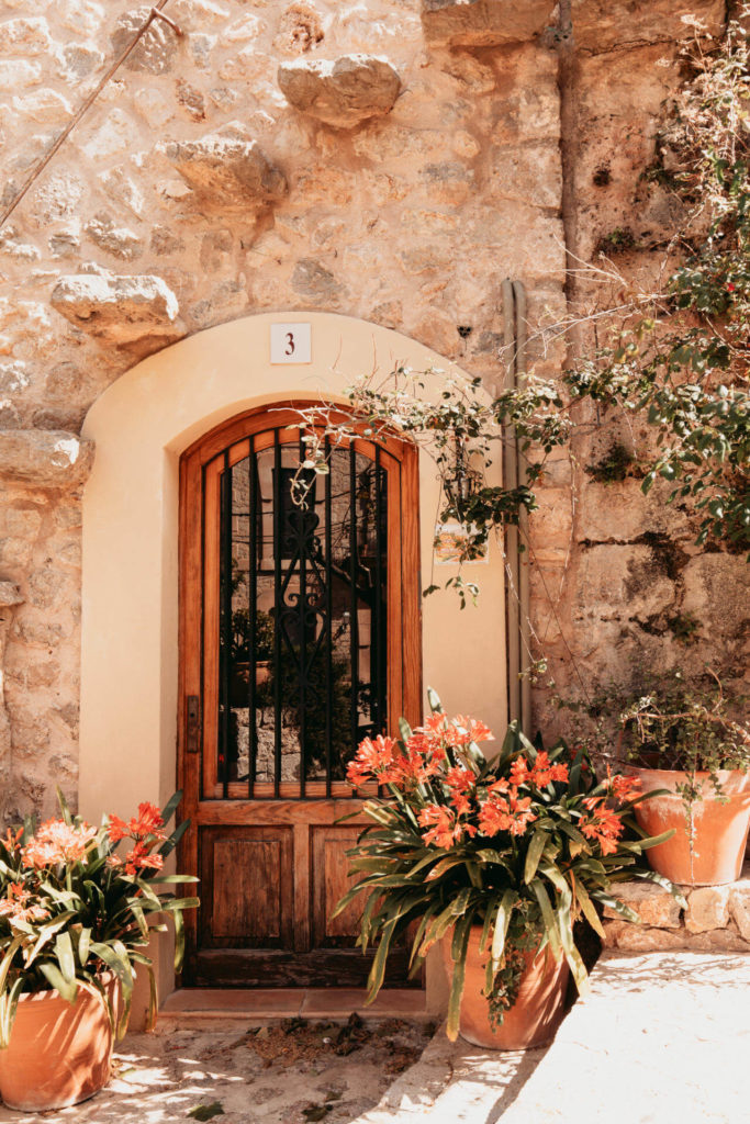 Eine mit Blumen geschmückte Tür in der Altstadt vom schönen ruhigen Ort Valldemossa auf Mallorca.