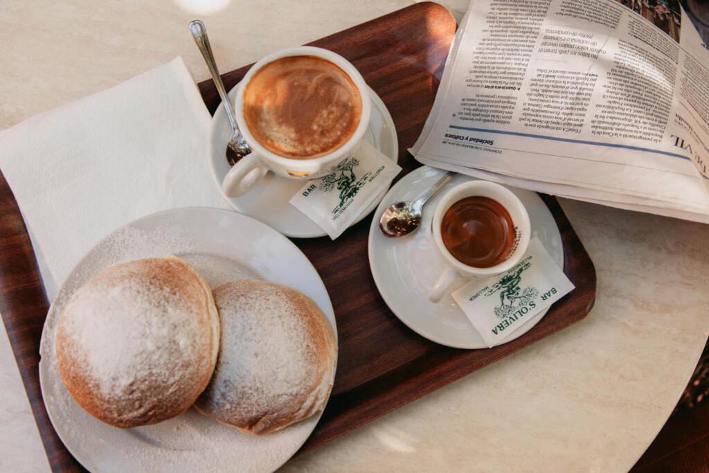 Hefebrötchen aus Kartoffelmehl, Cocas de Patata, mit Kaffee werden auf einem Holztablett in Mallorcas Ort Valldemossa serviert.