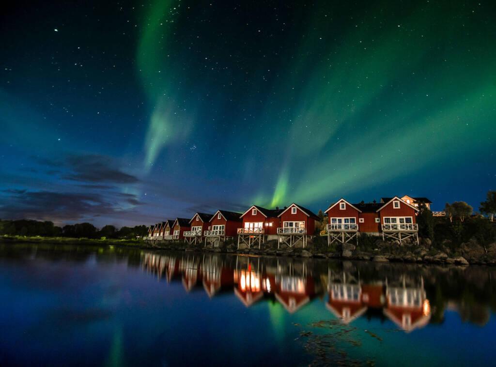 Die Polarlichter scheinen bei Nacht über eine Reihe an roten Hütten am Wasser