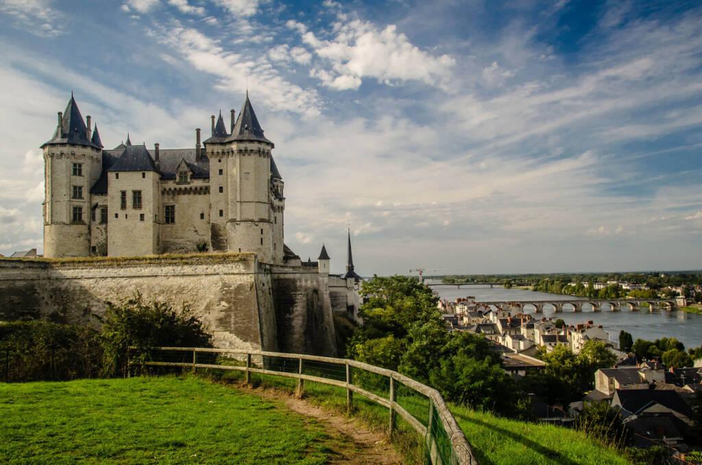 Eine Burg ragt über das Dorf darunter am Fluss