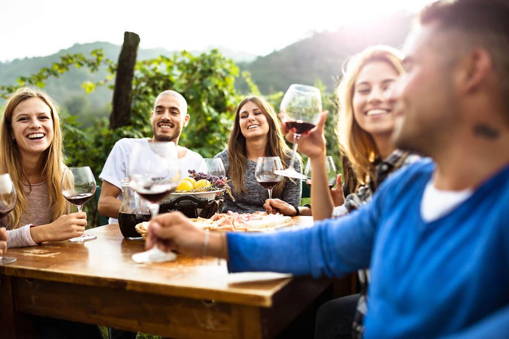 Eine Gruppe von jungen Menschen, die zusammen draußen fröhlich Wein trinken