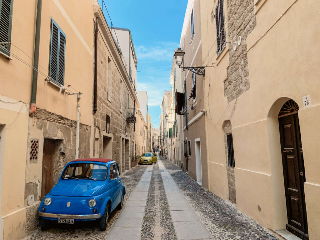 Ein süßes blaues Auto parkt in einer Straße der Altstadt von Alghero im Norden von Sardinien.