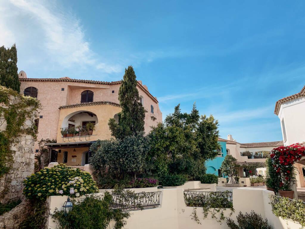 Das Gebäude der Piazzetta delle Chiacchiere in Sardinien ist von Blumen und Bäumen bewachsen.