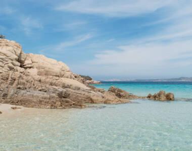Die Felsen am Strand von Cala Soraya im Norden von Sardinien ragen bis in das Wasser hinein.