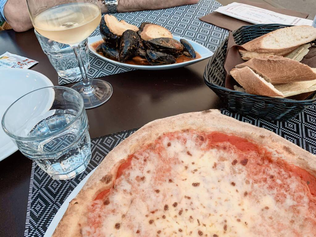 Eine Pizza von Pepebianco auf Sardinien mit Baguette, Muscheln und Wein.