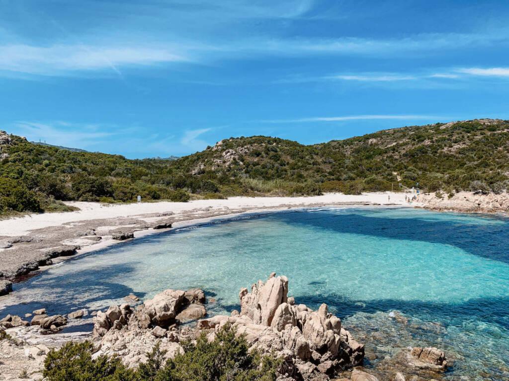 In der Bucht an der Spiaggia del Principe in Sardinien ist das strahlend blaue Wasser von Strand und Bergen umgeben.