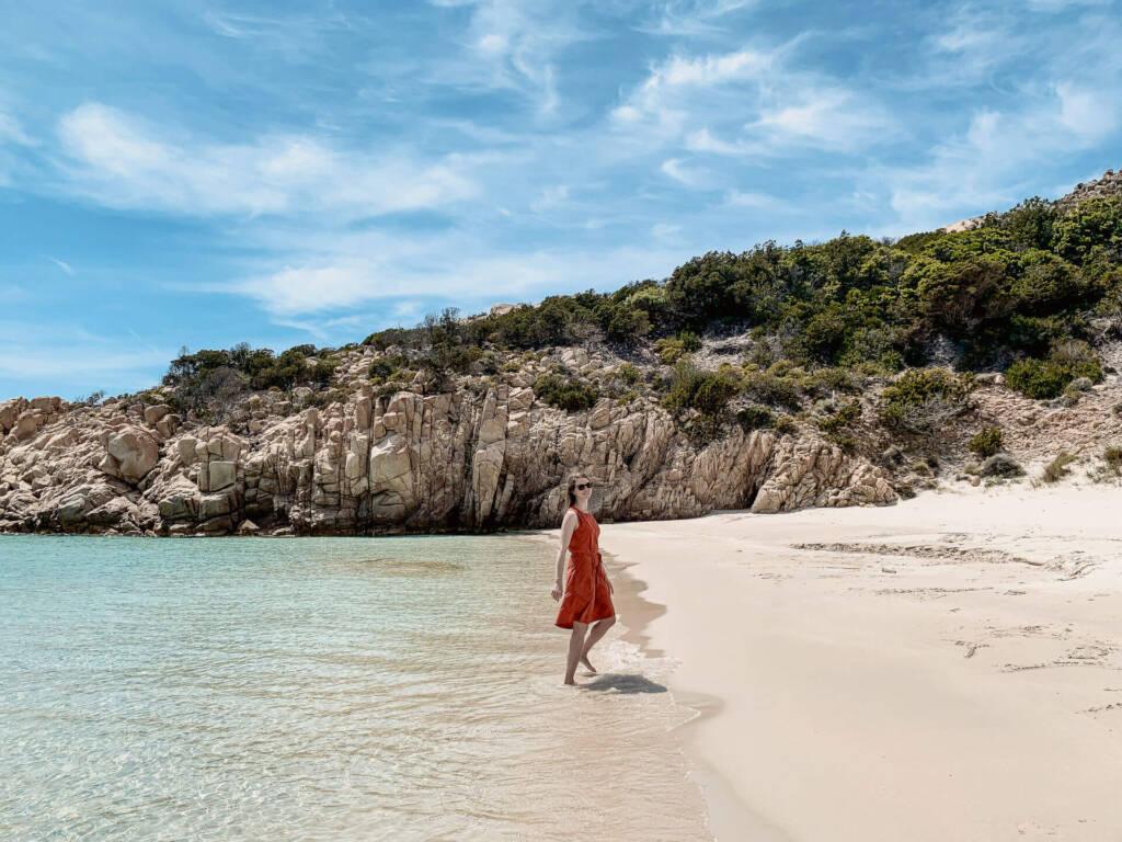 Franzi Reichelt von Coconutsports spaziert vor den Felsen am Strand der Cala Corsara auf Sardinien.