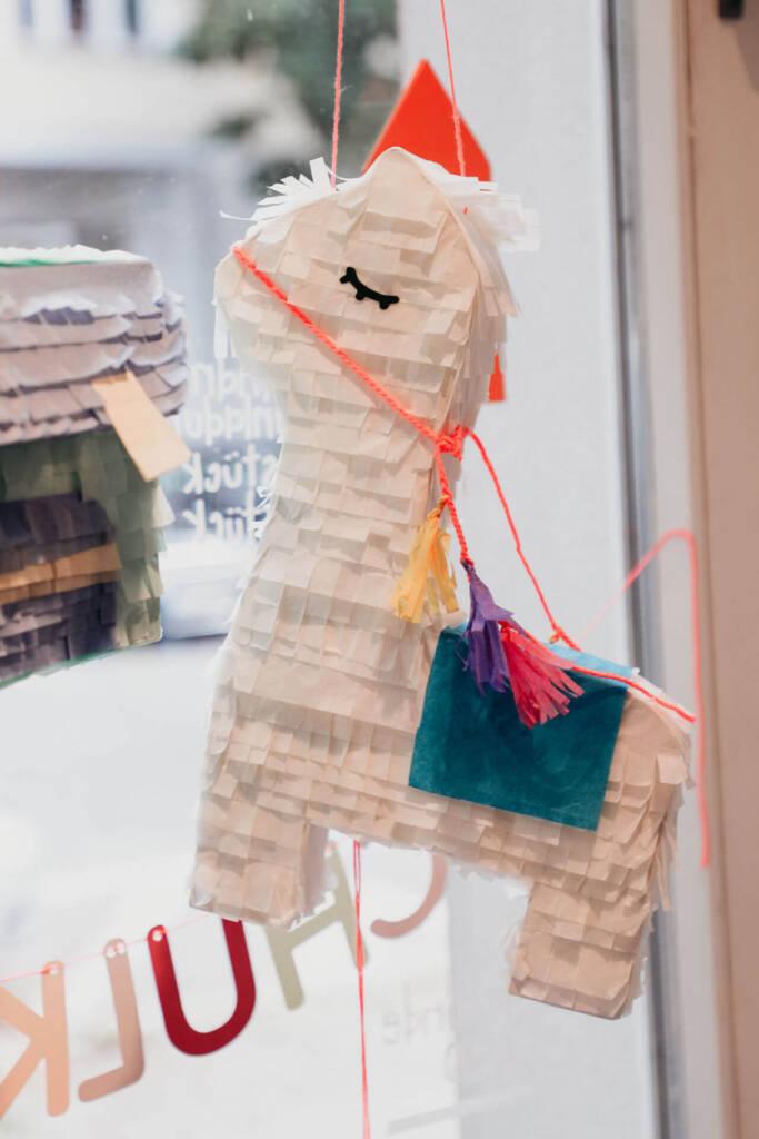 Eine Pinata hängt bei einLaden in Berlin am Fenster.