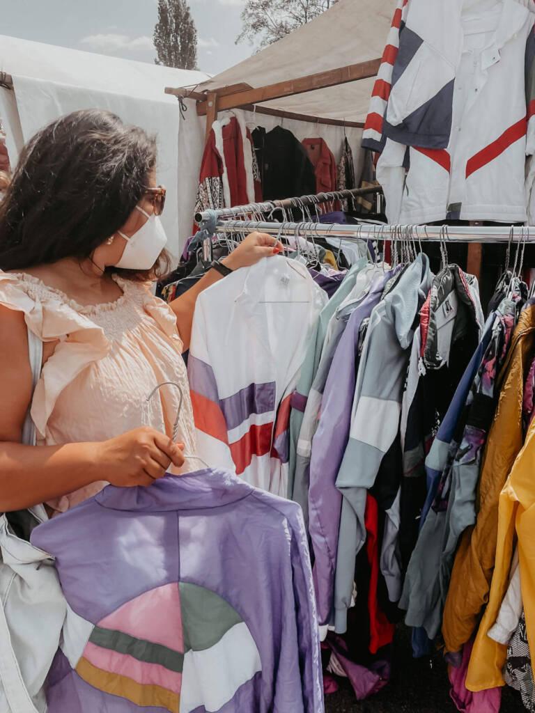 Tatiana von TheHappyJetlagger shoppt vintage Kleidung auf dem Mauerpark Flohmarkt in Berlin.