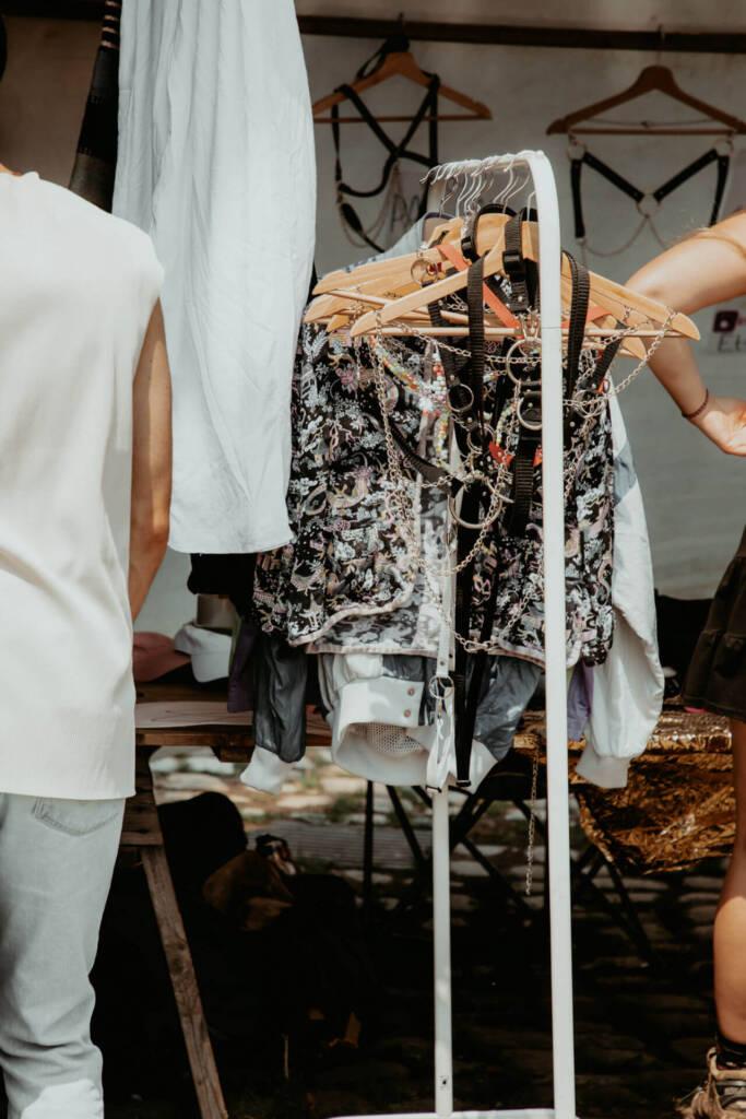 Einige Kleidungsstücke auf dem Mauerpark Flohmarkt hängen zur Präsentation auf der Kleiderstange.