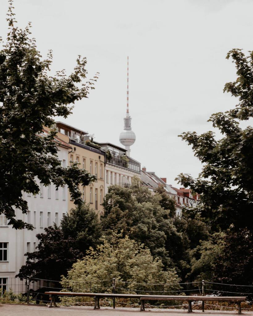 Die Aussicht vom Park oberhalb des Wasserturms auf den Berliner Fernsehturm zwischen den Häusern und Bäumen.
