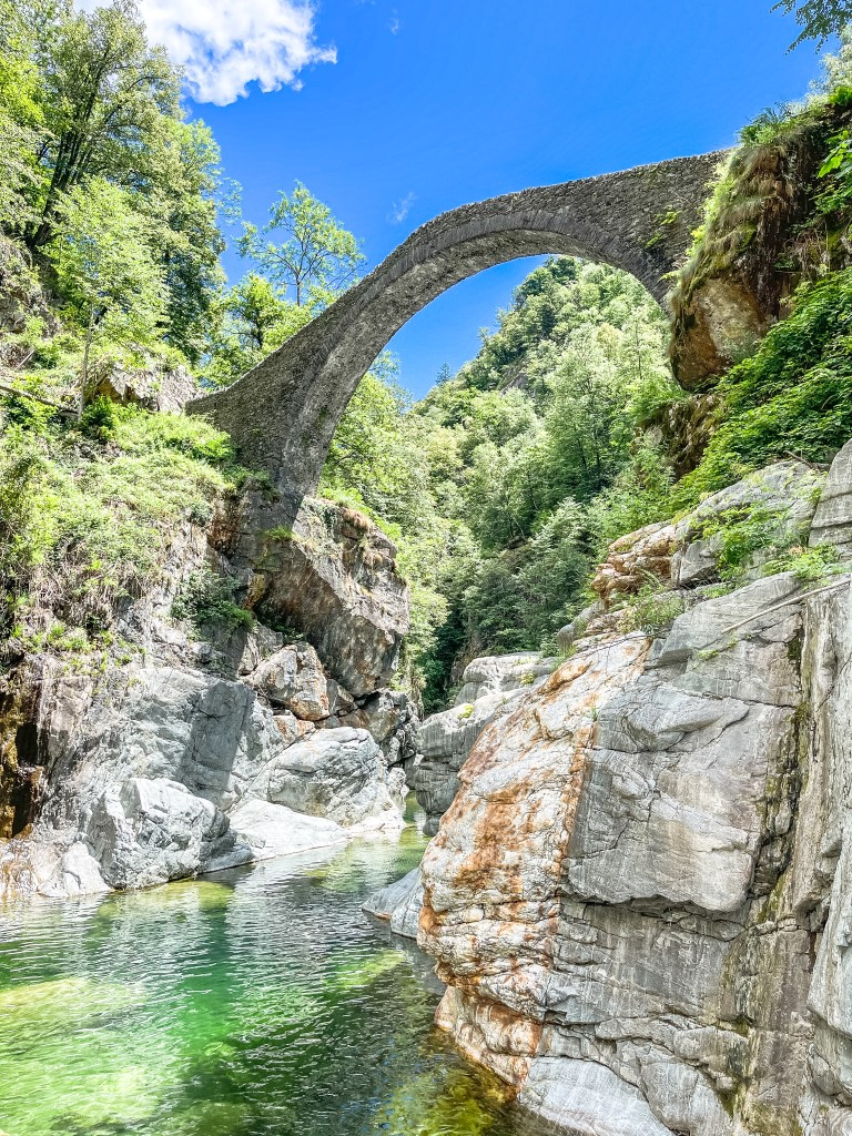 Das klare Wasser fließt unter der Römerbrücke im Centovalli.