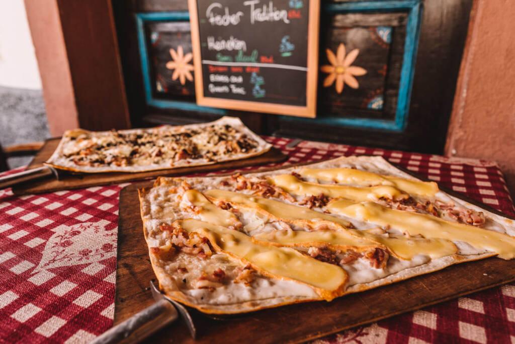 Schon längst kein Geheimtipp mehr: Flammkuchen mit saftigen Zwiebeln, herzhaften Speckwürfeln und würzigem Münsterkäse im Restaurant Le Baeckeoffe d'Alsace im La Petite France.