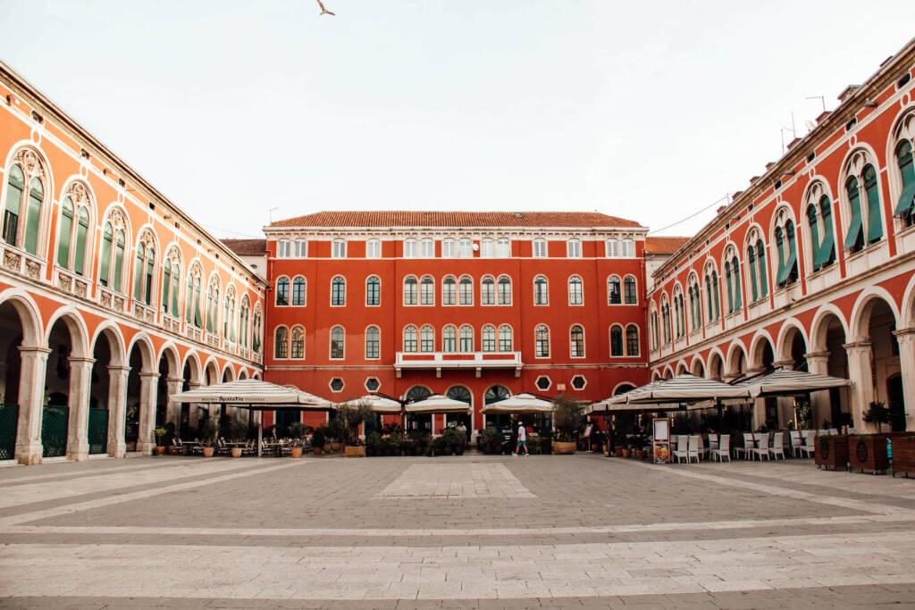 Der Platz der Republik in Split ist von prachtvollen roten Gebäuden umgeben.